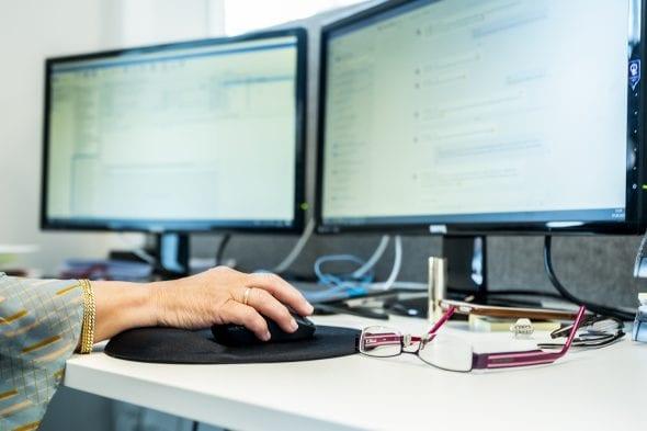 En hånd styrer en mus på et skrivebord foran to skjermer